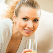 Young happy smiling woman drinking orange juice at home — Stock Photo #7543592