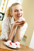 Portrait of young happy beautiful smiling blond woman eating cakes at home — Stock Photo