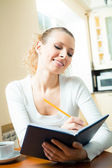 Young smiling woman with notebook or organiser at home — Stock Photo