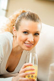 Young happy smiling woman drinking orange juice at home — Stock Photo