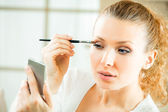 Young woman applying mascara with lash brush at home — Stock Photo