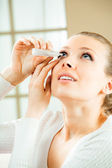 Photo of young woman dripping eye with eyes drops at home — Stock Photo
