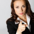 Serious business woman pointing finger at viewer, over grey — Stock Photo #7717588