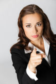 Serious business woman pointing finger at viewer, over grey — Stock Photo