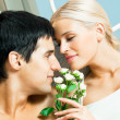 Happy couple with flowers at home — ストック写真