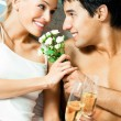 Stock Photo: Couple with champagne and flowers at bedroom