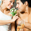 Couple with champagne and flowers at bedroom — Stock Photo