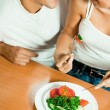 Foto Stock: Young happy couple eating salad