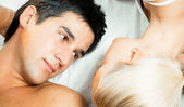 Young beautiful couple making love in bed — Stock Photo