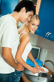 Young happy couple at kitchen — Stock Photo