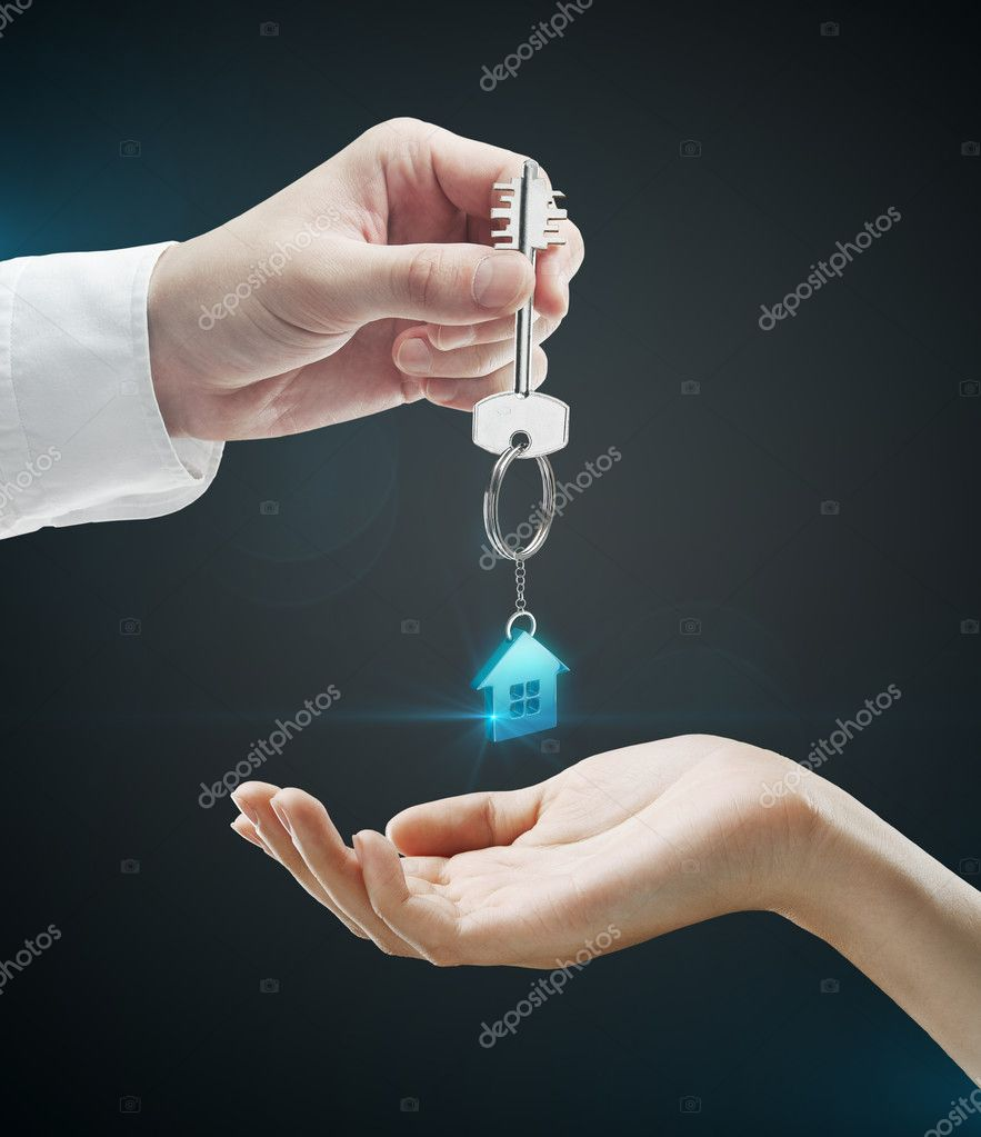 Man is handing a house key to a woman.Key with a keychain in the shape of the house. On a black background — Stock Photo #6887902