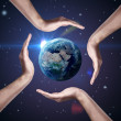 Conceptual symbol of the Earth with human hands around it. - Stock Photo