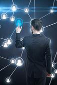 Young business man pressing a touchscreen Social Network button — Stock Photo