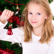 Stock Photo: Young girl with bell sit near Christmas tree.