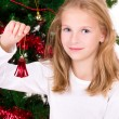 Young girl with bell sit near Christmas tree. — Stock Photo