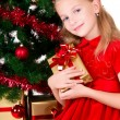 Young girl with gift sit near Christmas tree. - Stock Photo