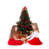 Two little girls sit near Christmas tree. — Stock Photo