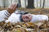 Young man with smile and mobil phone in autumun — Stockfoto