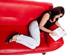 Reading a book on a sofa. — Stockfoto