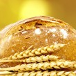 Artisan bread and wheat spikes background - Stock Photo