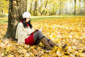 Beautiful woman reading the book in at autumn park — Stock Photo