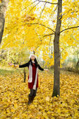 Young beautiful woman throwing the yellow leafs — Stock Photo