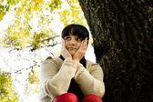 Retrato de joven sonriente sentado en la madera en el bosque — Foto de Stock