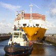 Container ship with tug boat in lock — Stock Photo