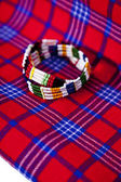 Colorful African bracelet with Masai blanket background — Stock Photo