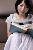 Young woman sitting on sofa reading book — Stock Photo