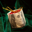 The Christmas toy wrapped in the dollar bill - Stock Photo