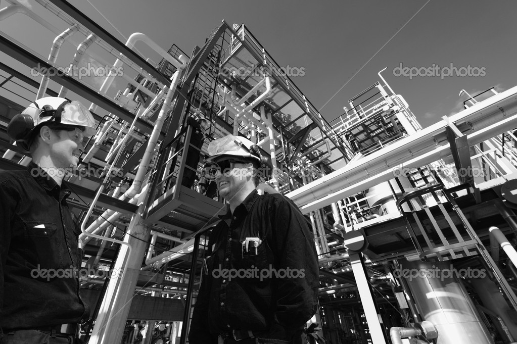 Two oil-workers, engineers with giant pipeline construction in background,dark silver duplex toning. — Stock Photo #6923822