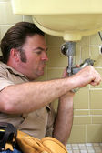 Plombier à l'aide de la clé à pipe — Photo