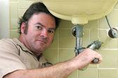 Plombier travaillant sous évier — Photo