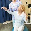 Physical Therapist Helps Senior Woman - Stock Photo