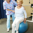 Physical Therapist Works with Senior - Stock Photo