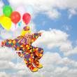 Clown flying with balloons — Stock Photo