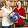 Teen Girls in Library with Globe — Stock Photo