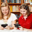 Teens Texting in Library - Stockfoto