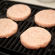 Stock Photo: Raw Turkey Burgers on Grill