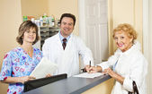 Doctor and Staff Greet Patient — Stock Photo