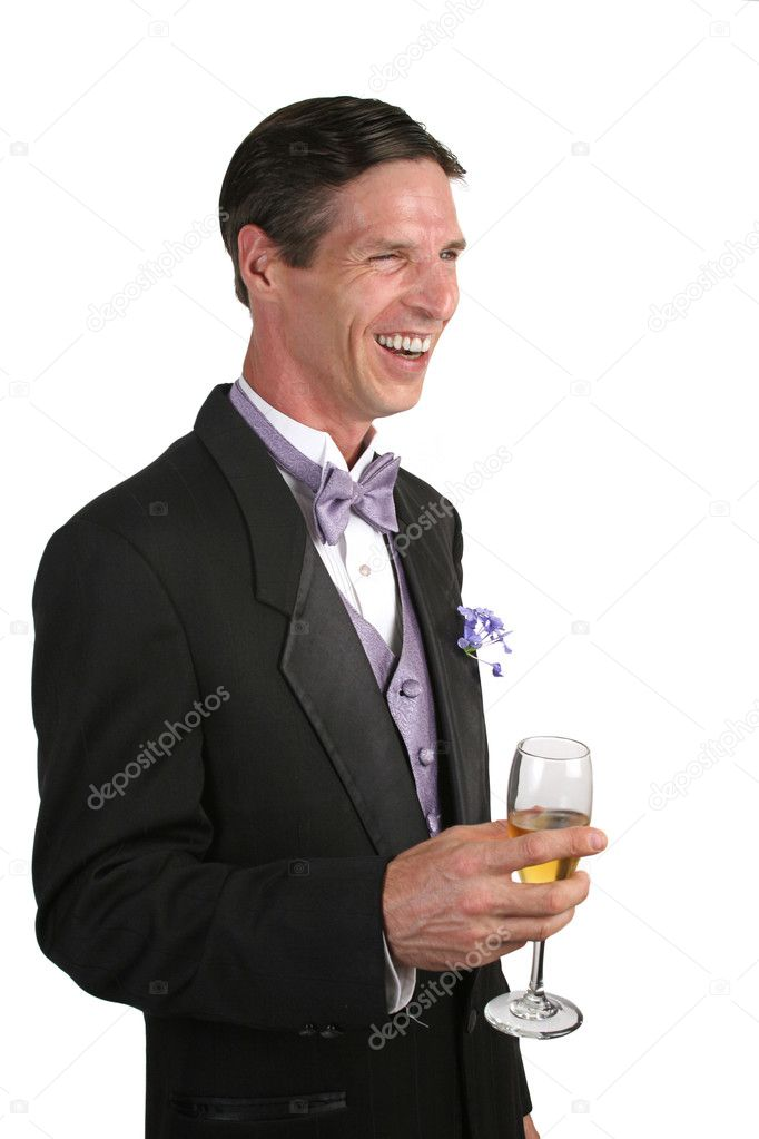 A handsome man in a tuxedo, with a glass of champagne, laughing at an amusing story. — Stock Photo #6800550
