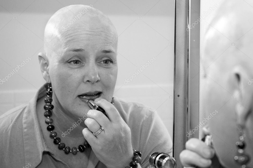 A woman bald due to a health issue, putting on makeup in the mirror.  — Stock Photo #6800612
