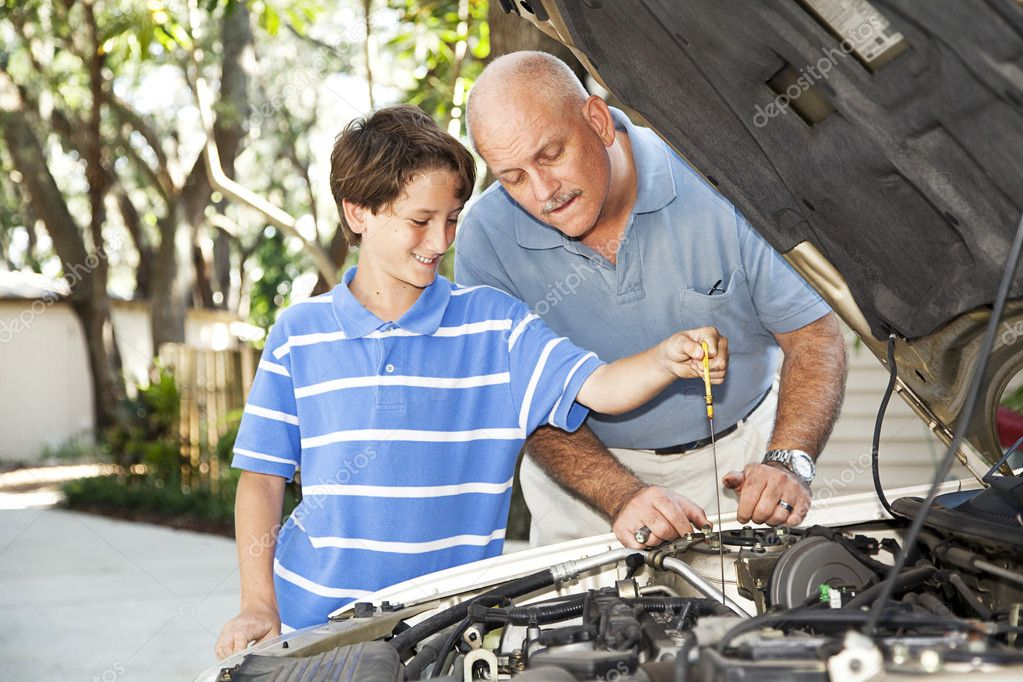 Father and son working on the car together.  The son is checking the oil.   — Stock Photo #6802629