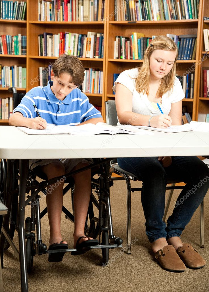 Disabled boy and a friend doing homework in the school library. — Stock Photo #6802640