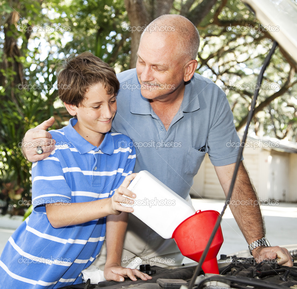Father teaches his son how to put oil in the family car.    Stock Photo #6802681