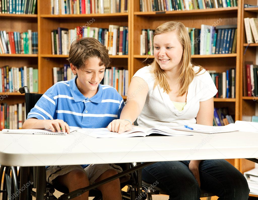 Teenage girl mentoring a younger, disabled boy in the school library.   — Stock Photo #6802756