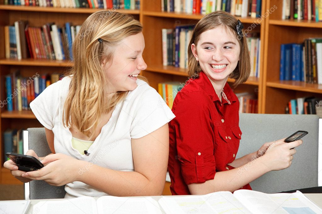 Teen girls having a conversation via text in the library.   — Stock Photo #6802818
