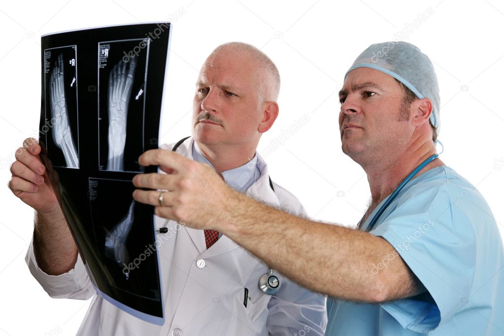 Two doctors examing the xray of a foot.  (focus on young doctor in foreground) — Stock Photo #6803243