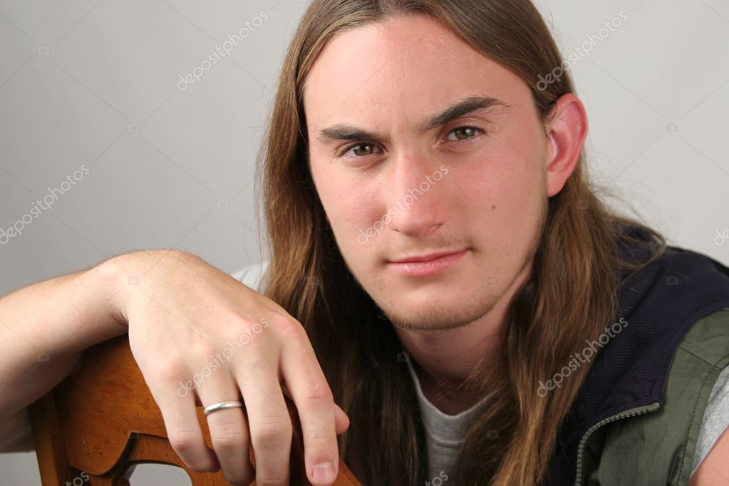 A handsome young man with long hair in a casual pose — Stock Photo #6803554
